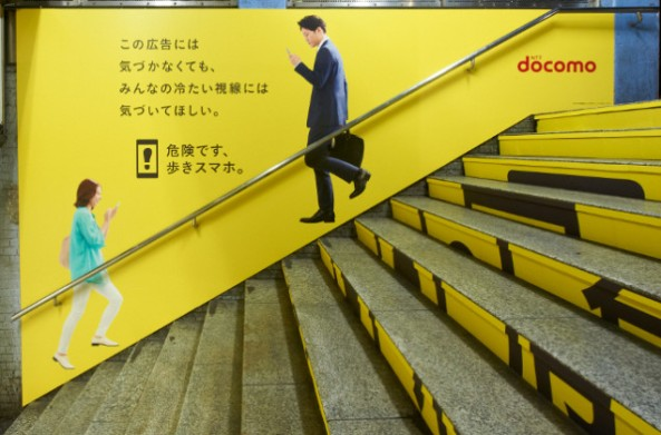 "Below, the text reads, ""Even if you don't notice this poster, we want you to notice everyone's icy stares.""   It reads, ""Walking while using a smartphone is dangerous."" P Under the warning, in parenthesis, it reads, ""But those people probably didn't see this announcement."""