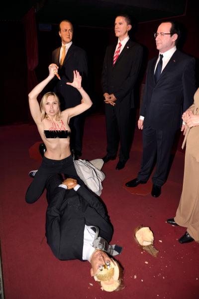 A Femen activist hacks apart Putin's effigy. (AFP)