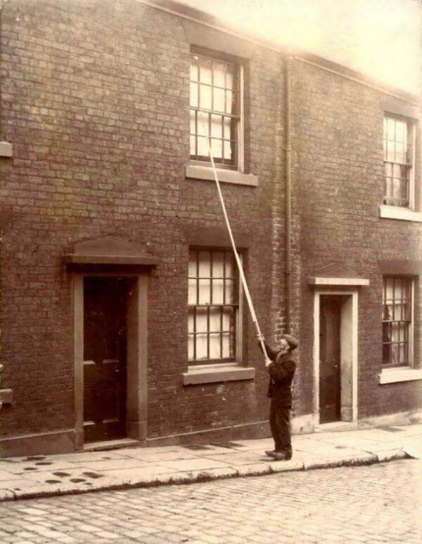 A  knocker-up  waking up clients - the early 20th century version of alarm clocks.