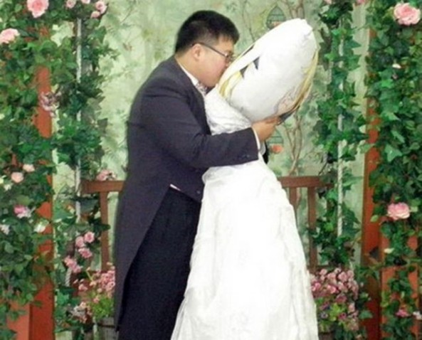 """South Korean Lee Jin-gyu fell in love with his body pillow of his favorite animated heroine, Fate Testarossa from the animated TV series Magical Girl Lyrical Nanoha. The two were dating for six years before Jin-gyu took her to Japan to get married, where Fate-the-pillow even donned her own wedding dress. Jin-gyu later confessed that the wedding was a publicity stunt, although marriage isn't completely out of the question and stated that, """"My love for Fate is unchangeable, but I will take more time to think about our marriage."""" His friends have said that the couple often go out together to parks and fairgrounds and the pillow gets its own seat when they dine together."""