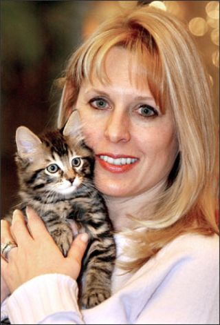 "ulie holds her 9-week-old clone, ""Little Nicky,"" yesterday in Texas. Little Nicky was sold to Julie by Genetic Savings and Clone for $50,000. She says its appearance and personality are identical to that of her previous cat."
