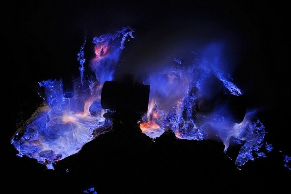 Electric blue flames caused by burning volcanic gases and molten sulfur. A night scene at the solfatara in the caldera of Kawah Ijen Volcano.