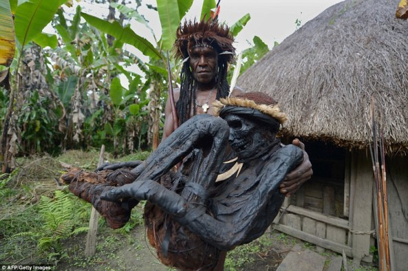 Dani tribe chief Eli Mabel is pictured holding the remains of Agat Mamete Mabel in the village of Wogi in Wamena in West Papua, an island in the centre of Papua New Guinea.