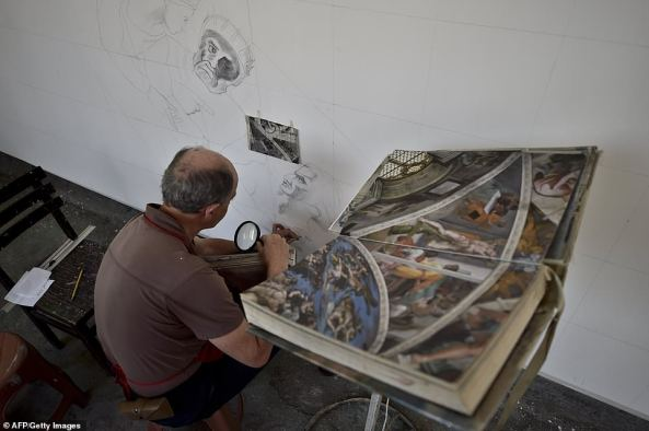 4. Assistant Gustavo Moreno uses a magnifying glass to ensure that the detail is recreated on the large canvas