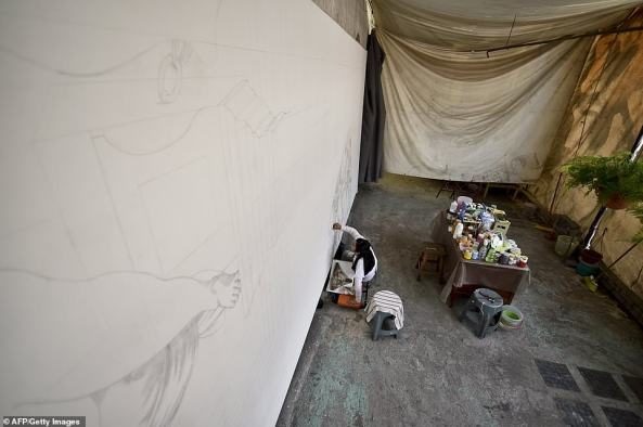 5. Assistant Elizabeth Ramirez works hard sketching out one of the Michelangelo murals on to a 45-foot wide canvas